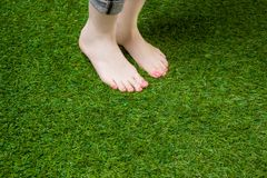 Woman legs standing  on green grass Stock Image