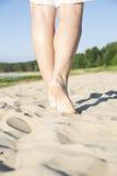 Woman legs step on warm sandy beach Stock Image