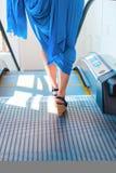 Woman legs stepping on an escalator stock image