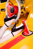 Woman legs on the stirring wheel of racing car Stock Images
