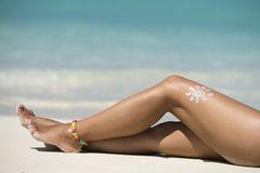 Woman legs with sun-shaped sun cream in the tropical beach conce. Ptual image of vacation Stock Photos