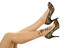 Woman legs tattoo on foot black heels out Stock Photo