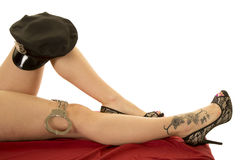 Woman legs with tattoo on foot handcuffs and cop hat Stock Photography
