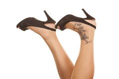 Woman legs tattoo on foot heels up Royalty Free Stock Photo