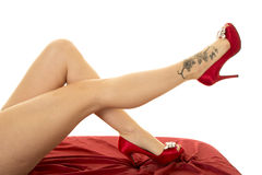 Woman legs tattoo on foot red heels and red sheet Royalty Free Stock Photo