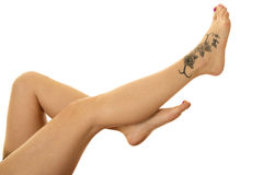 Woman legs with tattoo on foot up and out Royalty Free Stock Photo