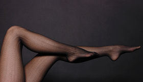 Woman legs in tights. Woman sexy legs in tights on black background Royalty Free Stock Photo