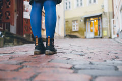 Woman legs in tights and leather boots on upward street. Shallow depth of field Stock Image