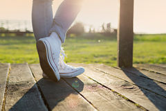 Woman legs in trainers. Woman's legs in trainers against the sunset stock images