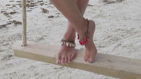 Woman legs on tree swing. Slow motion: woman legs and feet with anklet on wooden swing in Anse Volbert Cote d`Or beach , Praslin, Seychelles, Indian Ocean. close stock footage
