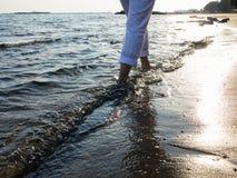 Woman legs walking along the sea coast Stock Photography