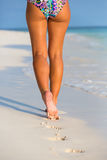 Woman legs walking on the beach Stock Images