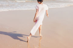 Woman legs walking on the beach sand Stock Photos