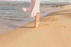 Woman legs walking on the beach sand Royalty Free Stock Photo