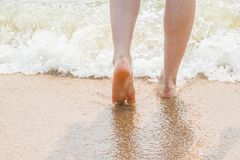 Woman legs walking on the beach sand Stock Images
