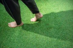 Woman legs walking on green grass royalty free stock image