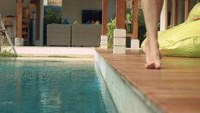 Woman legs walking near swimming pool