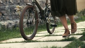 Woman legs walking beside riding bike on city road. Woman feet and bicycle wheel stock video footage