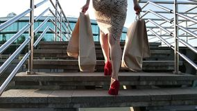 Woman legs walking on stairs with shopping bags stock video