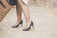 Woman legs wearing black high heel shoes Stock Photos