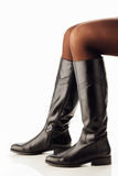 Woman legs wearing black leather high boots Royalty Free Stock Images