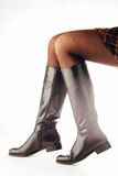 Woman legs wearing black leather high boots Stock Images