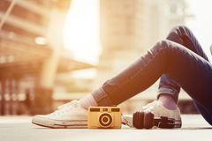 Woman legs wearing jeans and resting and relax in middle of city. Vintage camera and Stereo headphones elements Fashion and Modern stock photo