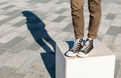 Woman legs wearing skinny brown trousers and black sneakers Royalty Free Stock Images