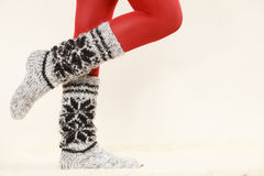 Woman legs wearing woolen socks and red tights Royalty Free Stock Photo