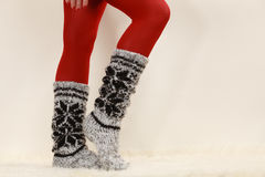 Woman legs wearing woolen socks and red tights Stock Images