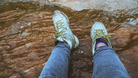 Woman legs wearshoes walk in the forest wade water. Trekking, traveling, playing in the natural stream royalty free stock image