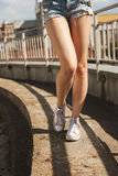 Woman legs in white gumshoes Royalty Free Stock Images