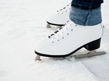 Woman legs in white ice skates Stock Images