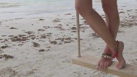 Woman legs on wooden swing. SLOW MOTION: woman legs swinging on tree swing on tropical beach under coconut palm trees of Anse Volbert Cote d`Or, Praslin stock video