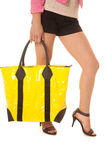 Woman legs yellow bag hold down Stock Image