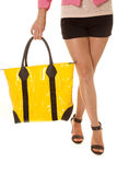 Woman legs yellow bag hold legs crossed Stock Image