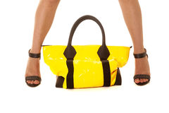 Woman legs yellow bag sit between Royalty Free Stock Image