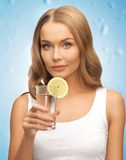 Woman with lemon slice on glass of water Stock Photography