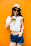 Woman with lemonade or fresh  in sunglasses and hat over orange colorful background Royalty Free Stock Photo
