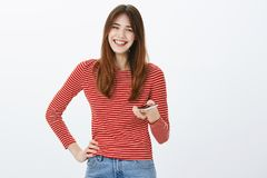 Woman lending phone for friend to call mom. Portrait of friendly-looking happy young female student in casual outfit stock photography