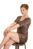 Woman leopard dress cross legs hands knees Stock Photo
