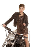 Woman leopard dress jacket stand on motorcycle look Royalty Free Stock Image