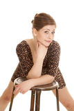 Woman leopard dress lean over stool Royalty Free Stock Photos
