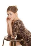 Woman leopard dress lean on stool side Royalty Free Stock Photos