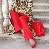 A woman in a leopard fur coat or coat. Red shoes and bag. Points in the hands of a lady. Close-up. Gift vouchers, Black Friday, Cyber Monday, Boxing Day Royalty Free Stock Image