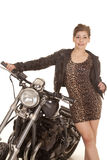 Woman leopard print dress stand by motorcycle Stock Image