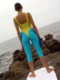 Woman in leotard. A Girl doing workout at the sea stock photo