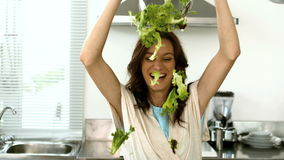 Woman lets fall lettuce while preparing a salad stock video footage