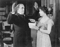Woman with a letter in her hand pointing at a man Stock Image