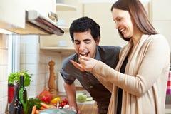 Woman letting man taste a soup. Smiling woman letting man taste a soup with a wooden spoon in the kitchen Royalty Free Stock Photo